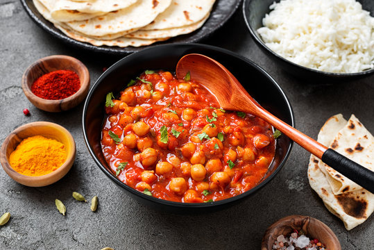 Traditional Indian dish chickpea chana masala with rice and flatbread.