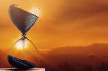 Falling sand in a hourglass with twilight sky background Fototapete