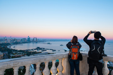 Couple traveler use smart mobile phone and camera take photo of view of Baku caspian sea and Baku sky scape view in sunset at Buku view point with copy space.