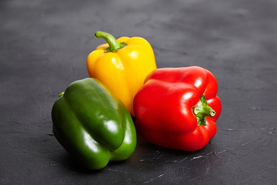 Red, green, and yellow bell peppers on  black background. Three sweet peppers in different colors on stone table, vegetable ingredient, healthy food