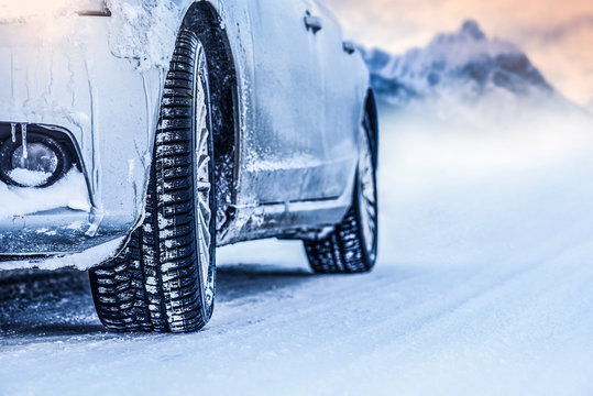 Luxus car on winter frozen road. Tires on snow. Winter tire in mountines.
