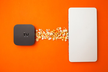 Remote control devices concept. Set of controller and micro console for TV watching and online streaming. Popcorn and snacks on the orange background. Top view. Space for a text. Close up.