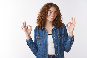 Outgoing friendly happy smiling redhead freckled girl pimples wearing denim jacket laughing having fun feeling awesome show okay ok cool gesture pleased good perfect result, white background