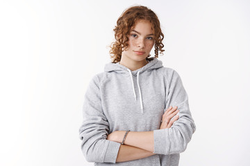 Serious-looking attractive young teenage sportswoman with ginger hair freckles wearing hoodie cross arms self-assured strong pose dressed-up morning jogging, standing white background assertive