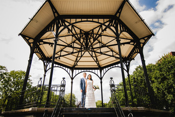 A mixed race/ethnicity couple pose under a public gazebo on their wedding day