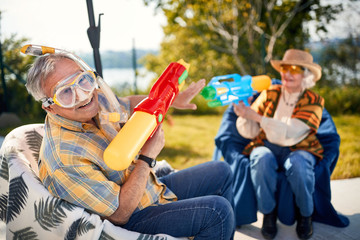 Funny holiday.Senior couple   playing with water gun