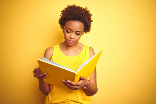African american woman reading a book over yellow isolated background with a confident expression on smart face thinking serious