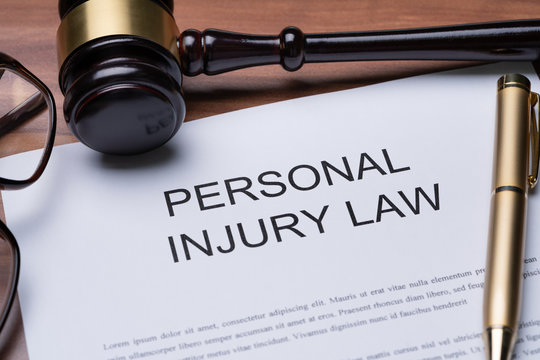 Gavel, Spectacles And Pen On Paper Of Personal Injury Law