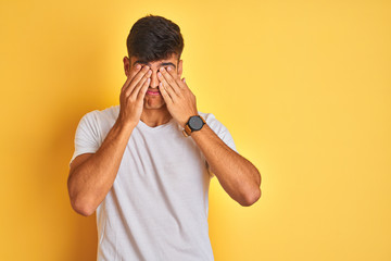 Young indian man wearing white t-shirt standing over isolated yellow background rubbing eyes for fatigue and headache, sleepy and tired expression. Vision problem Fotomurales