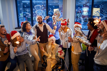 happy business team in santa hats celebrating holiday at work.Merry Christmas and Happy New Year