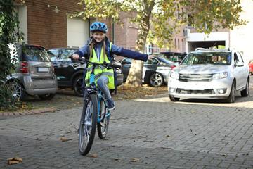 Kind auf einem Fahrrad biegt in eine Richtung ab