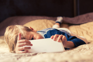 Small boy with touchpad lying down on bed at home.