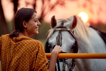 Pretty woman smiling in front of her horse in the sunset