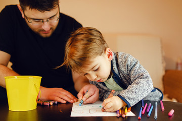 Small boy and his uncle or father sitting by the table at home playing with crayons color pencils drawing and learning family activities having fun