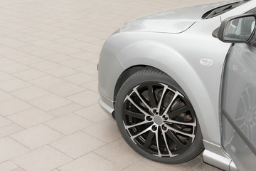 Wheel and rims of a sporty car in gray or silver.