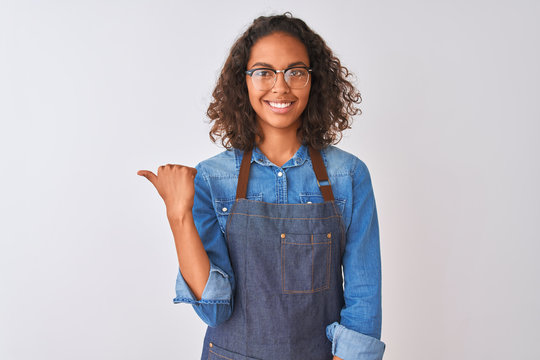 Young brazilian chef woman wearing apron and glasses over isolated white background smiling with happy face looking and pointing to the side with thumb up.