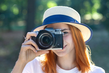 Pretty teenage girl with red hair taking picture with photo camera in summer park.