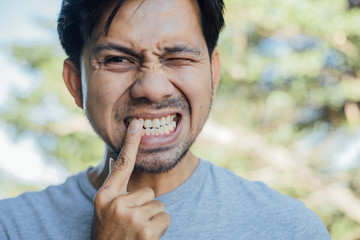 young man has strong toothache and suffering from pain ,Feel toothache