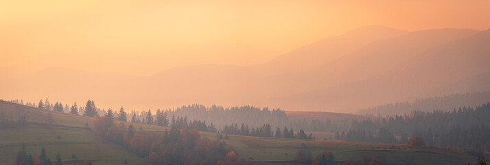 Keuken foto achterwand Beige Beautiful autumn scenery of foggy valley at Carpathian mountains at early morning before sunrise. Grass hill with yellow trees on foreground.