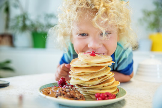 Little curly boy eating sweet pancakes