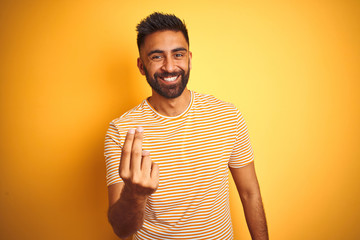 Young indian man wearing t-shirt standing over isolated yellow background Beckoning come here gesture with hand inviting welcoming happy and smiling