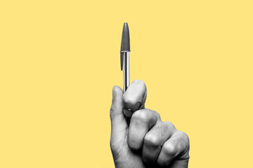 Concept of freedom of speech and information, stop censorship. Hand holding a pen in sign of protest, the pressure of censorship. Yellow background. Black and white image