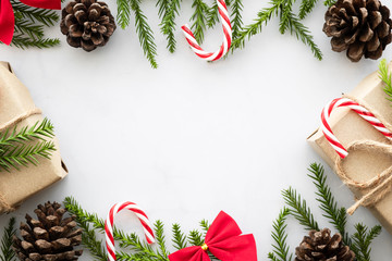 White marble table with Christmas decoration including giftbox, candy cane, pine branches and pine cones. Merry Christmas and happy new year concept. Top view with copy space, flat lay.