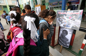 Colleagues of Palestinian schoolchildren of Abu Malhous family, who were killed in Gaza, react as they look at their pictures at their school in the central Gaza Strip