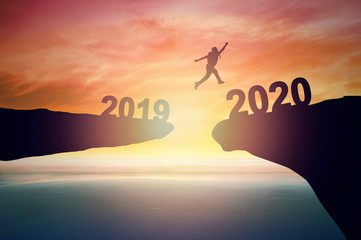 Jump to 2020 new year concept, silhouette of man jumping over  barrier cliff and success Wall mural
