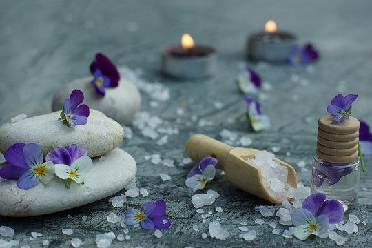 Set for spa treatments on a marble tabletop with purple pansy flowers