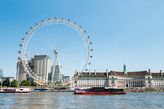 London, UK - June 25, 2018: Sightseeing tour boat on Thames river by London Eye, City Hall at Victoria Embankment in sunny summer