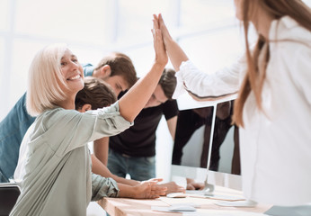 smiling employees giving each other a high five