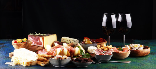Italian antipasti wine snacks set. Cheese variety, Mediterranean olives, seafood salad, Prosciutto di Parma, tomatoes, anchovy and wine in glasses