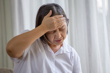 Asian senior woman sitting on sofa having headache at home. old female   stressed dizzy . elderly touching her head with her hands while having migraine or alzheimer .memory loss . indoor. copy space