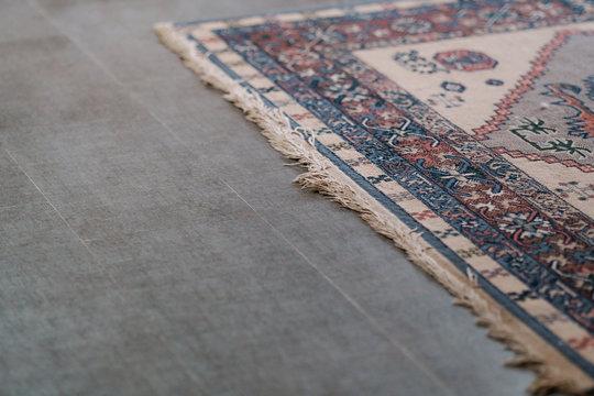 Ornamental design carpet on grey tile floor. Interior minimalist details