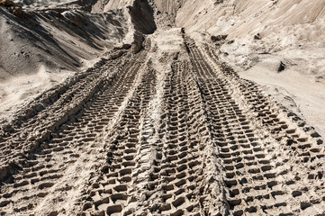 Earth mover tire tracks in sand quarry