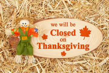 Closed for Thanksgiving message with a scarecrow with wood sign