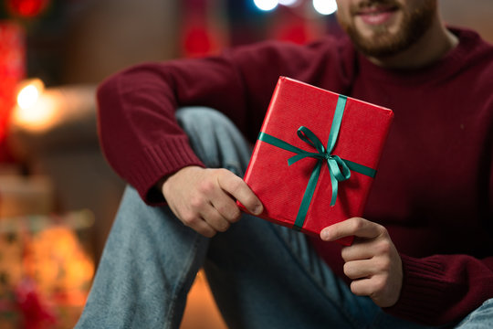 man with christmas gifts under the tree