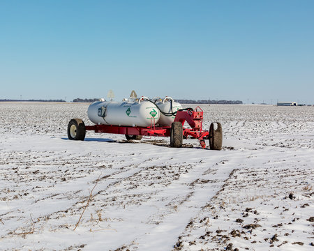 Anhydrous ammonia fertilizer tanks and wagon in harvested soybean farm field covering in snow after an early winter snowstorm