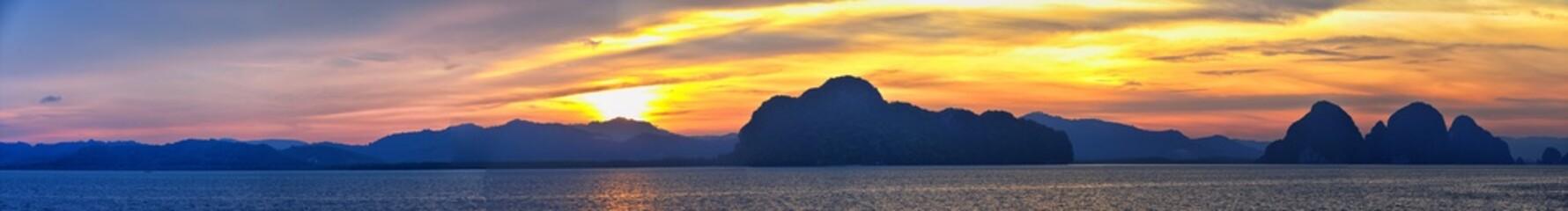 Islands Sunset, Ocean panorama views near Phuket with deep Red, Orange, Purple and Blue, mountains, twilight in Thailand. Including Phi Phi, Ko Rang Yai, Ko Li Pe and other islands. Asia.