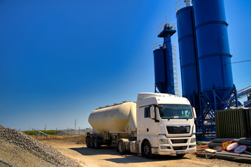The truck near the concrete station. Asphalt production, Road construction. Blue sky background.