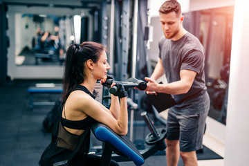 Fit woman working out with trainer at the gym. Athlete and beauty doing workout. Health life sport concept.