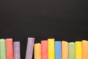 Group of colorful chalks and a blackboard or chalkboard background, concept for education, back to...