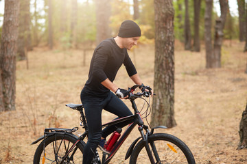 Young sporty biker riding on bike in inspirational forest landscape. Man cycling MTB on enduro trail path, covering assigned distance, wearing black sport wear and cap, enjoying active recreation.