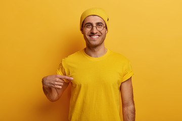 Half length shot of cheerful man points at mockup yellow t shirt, shows space for your design, has...