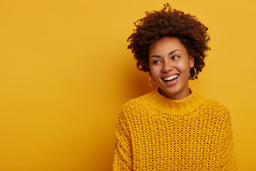 Tender charming happy curly woman has relaxed joyful face expression, Afro hairstyle, wears knitted sweater, laughs enthusiastic, poses against yellow background, blank space aside, turns away