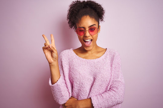 African american woman wearing winter sweater and sunglasses over isolated pink background smiling with happy face winking at the camera doing victory sign. Number two.