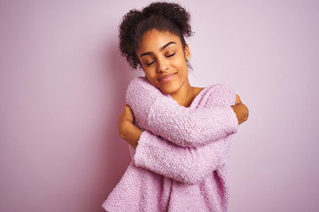 Young african american woman wearing winter sweater standing over isolated pink background Hugging oneself happy and positive, smiling confident. Self love and self care