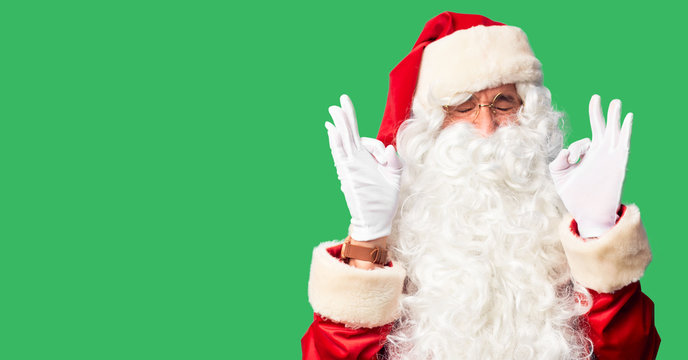 Middle age handsome man wearing Santa Claus costume and beard standing relaxed and smiling with eyes closed doing meditation gesture with fingers. Yoga concept.