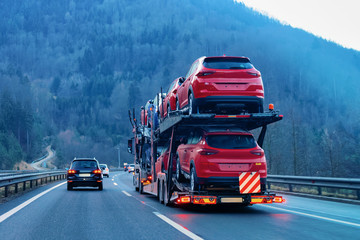 Red Car carriers transporter truck on road. Auto vehicles hauler on driveway. European transport logistics at haulage work transportation. Heavy haul trailer with driver on highway.